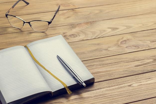 Caneta no caderno e óculos na mesa de madeira clara. copie o espaço