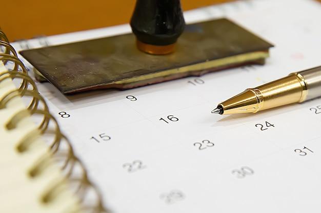 Caneta no calendário para evento de negócios de finalidade do planejador.
