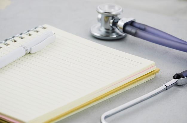 Caneta no diário com estetoscópio no pano de fundo cinzento