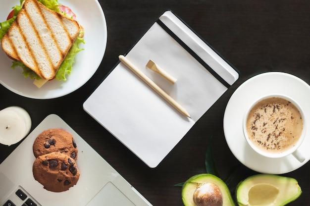 Caneta no diário em branco com sanduíche; biscoitos; abacate e xícara de café em fundo preto