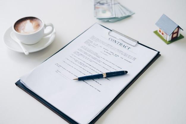 Caneta no documento de seguro de casa e documento do contrato perto de xícara de café
