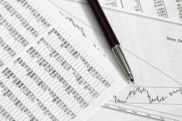 Caneta no papel com as cotações de preços e gráficos a dinâmica de sua mudança e moedas