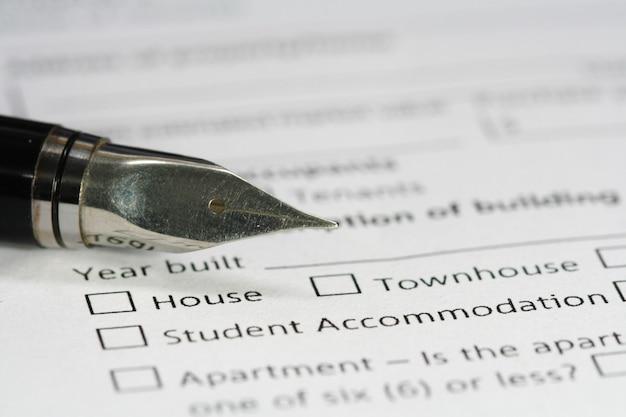 Caneta no papel de documento de habitação