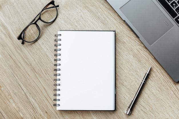 Caneta, óculos e bloco de notas na mesa de madeira conceito de negócio