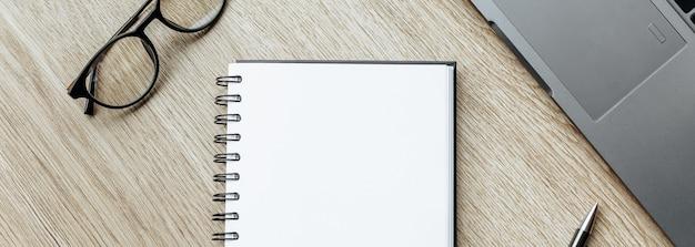 Caneta, óculos e bloco de notas na mesa de madeira