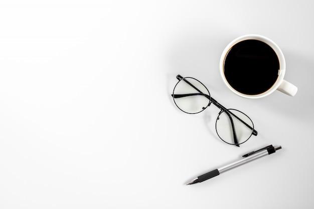 Caneta, óculos e xícara de café na mesa branca. - trabalhe do conceito de casa.