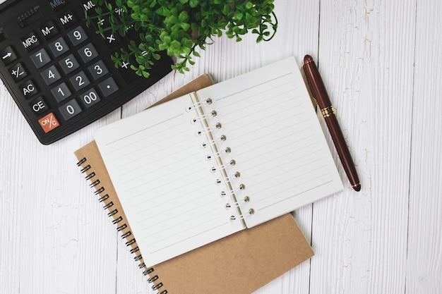 Caneta ou caneta de tinta com papel de caderno e calculadora na madeira