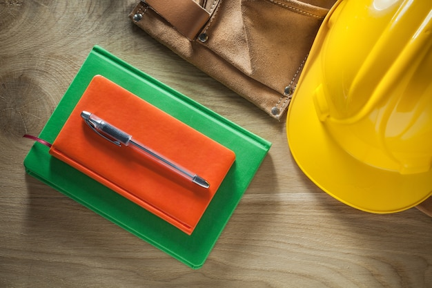 Caneta para cadernos, cinto de ferramentas de couro, capacete na placa de madeira
