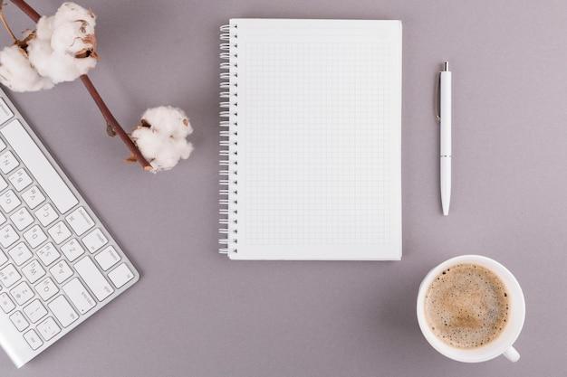 Caneta perto de bloco de notas, teclado, galho e copo