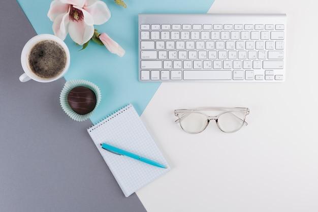 Caneta perto de caderno, xícara, biscoito, flor, óculos e teclado