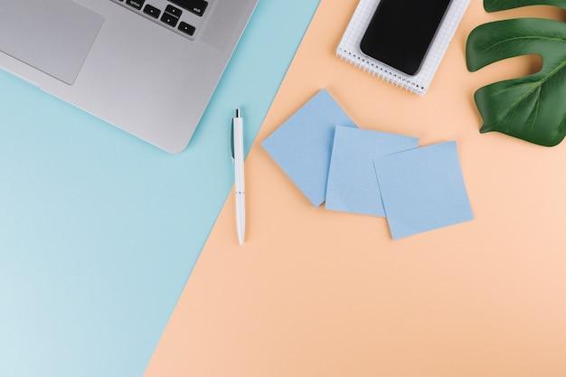 Caneta perto de papéis, bloco de notas, smartphone, planta e laptop