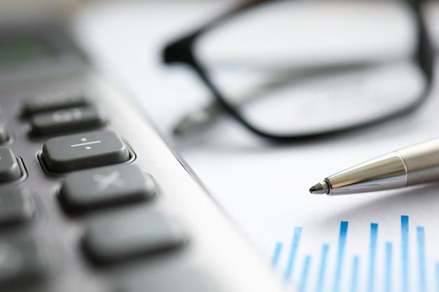 Caneta prata com gráfico de papel e óculos deite-se na mesa de escritório