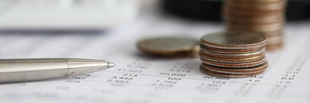 Caneta prata sobre papel de estatísticas financeiras com conjunto de números close-up