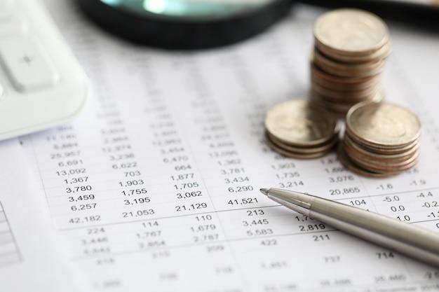 Caneta prata sobre papel de estatísticas financeiras com conjunto de números