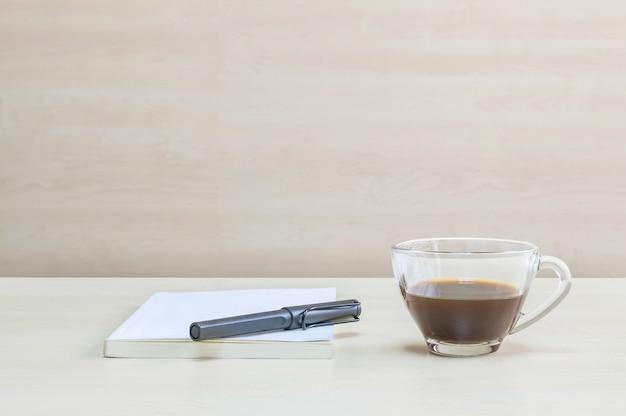 Caneta preta closeup no livro branco com café preto na mesa na sala de reunião