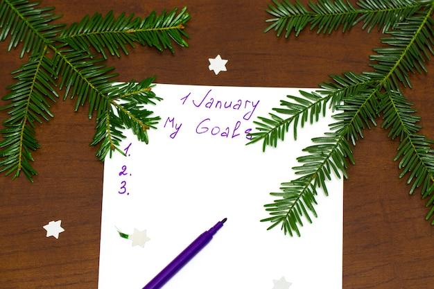 Caneta roxa e bloco de notas para escrever resoluções e metas para o ano novo, ramos verdes de uma árvore de natal