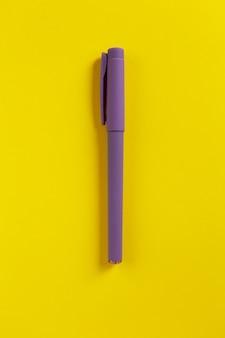 Caneta roxa em papel amarelo