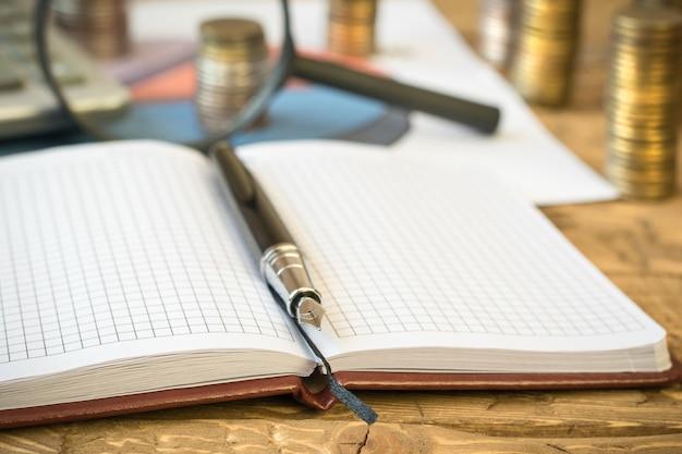 Caneta-tinteiro, calculadora, moedas e caderno em uma mesa de madeira.