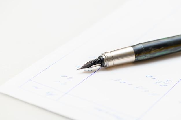 Caneta-tinteiro com pena de aço em papel branco