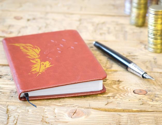 Caneta-tinteiro, moedas e caderno em uma mesa de madeira.