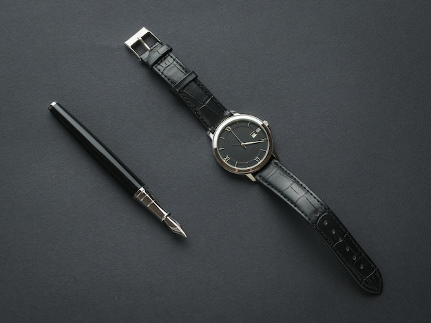 Caneta-tinteiro preta e relógio preto masculino com as mãos em um fundo preto. assuntos para homens.
