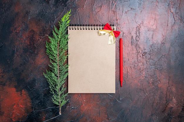 Caneta vermelha de vista superior em um bloco de notas com um pequeno arco um galho de pinheiro em uma superfície vermelha escura com espaço de cópia