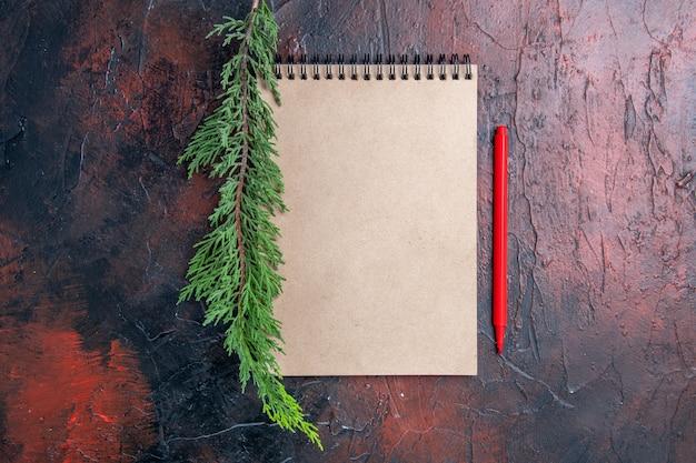 Caneta vermelha de vista superior, um bloco de notas com um pequeno arco, um galho de pinheiro na superfície vermelha escura com espaço de cópia