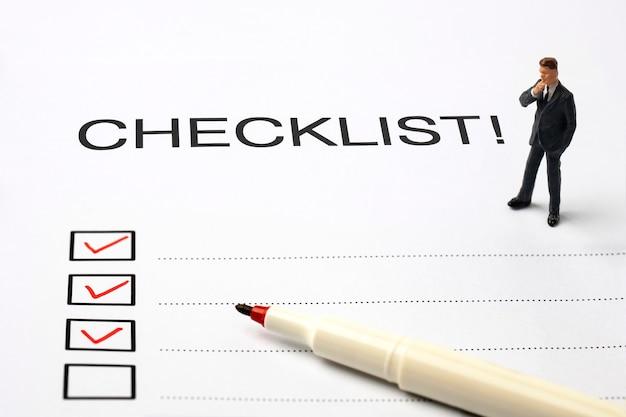 Caneta vermelha marcando na caixa da lista de verificação com o homem de negócios em miniatura