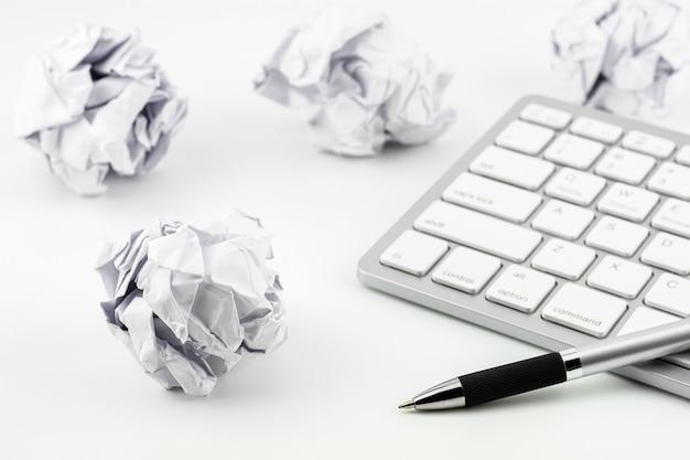 Canetas colocadas no teclado do computador e bolas de papel amassado em uma mesa branca