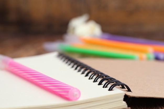 Canetas coloridas e livro