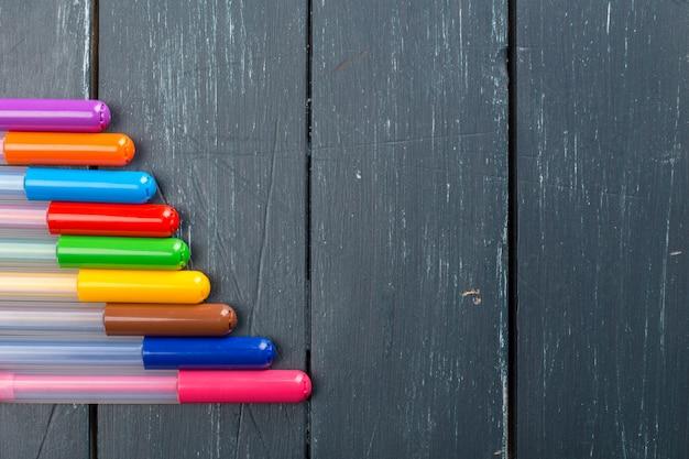Canetas coloridas em fundo madeira