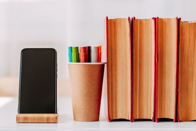 Canetas coloridas no frasco de papel artesanal na mesa branca. material escolar. grandes livros vermelhos e smartphone em cima da mesa.