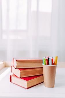 Canetas coloridas no frasco de papel artesanal na mesa branca. material escolar. grandes livros vermelhos em cima da mesa.