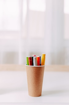 Canetas coloridas no frasco de papel artesanal na mesa branca. material escolar.