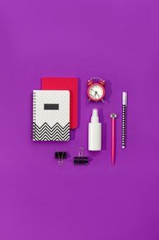 Canetas de cadernos e despertador na mesa roxa moderna
