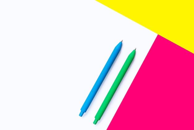 Canetas de cor azul verde em fundo branco com elementos rosa e amarelos.