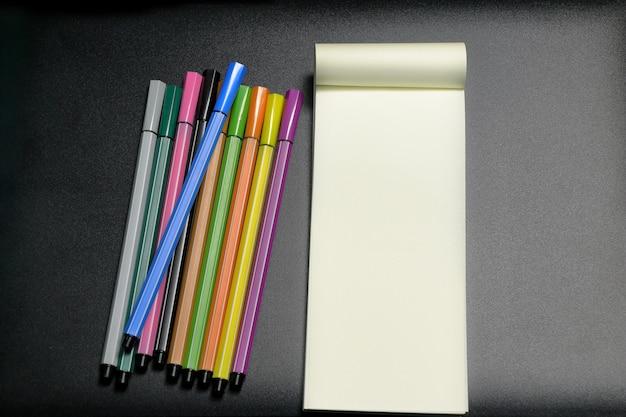 Canetas de cor e papel de nota em fundo escuro