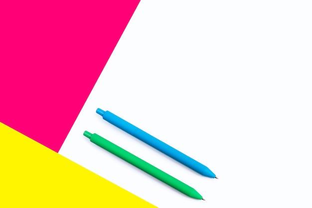 Canetas de cor em fundo branco com elementos rosa e amarelos.