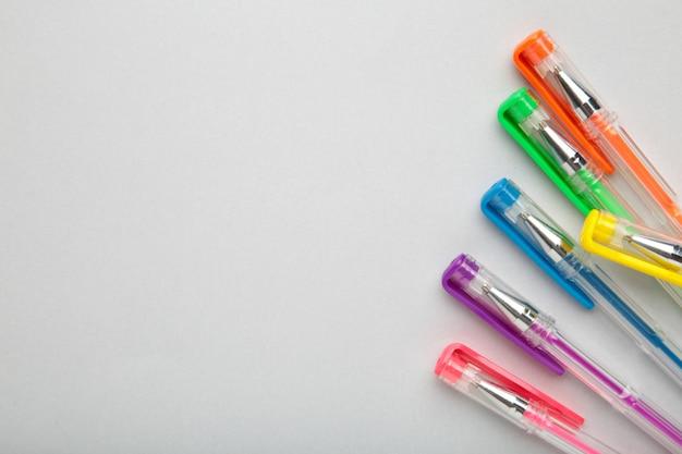 Canetas de cores diferentes na superfície cinza com espaço de cópia