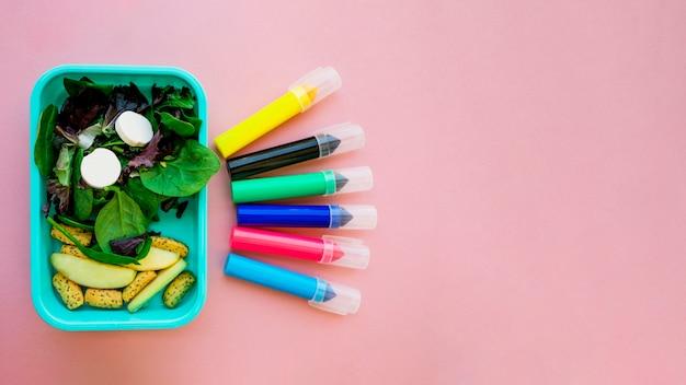 Canetas de marcador deitado perto de salada