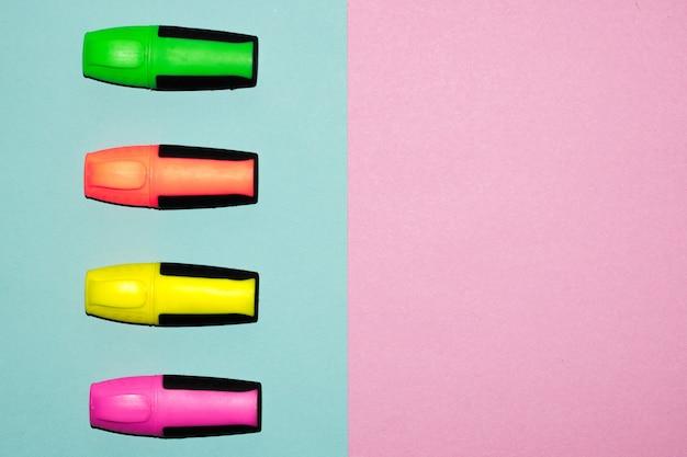 Canetas de ponta de feltro multicoloridos em rosa pastel e fundo azul pastel. marcadores coloridos