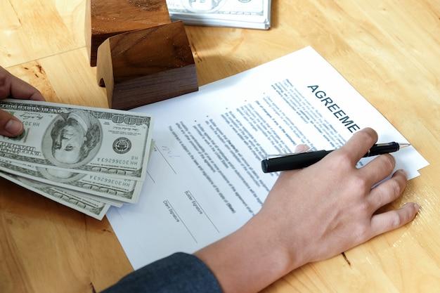 Canetas e dólares na mão com documentos de acordo e casas modelo.