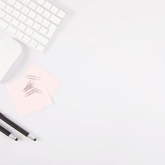 Canetas e notas adesivas perto de teclado e mouse