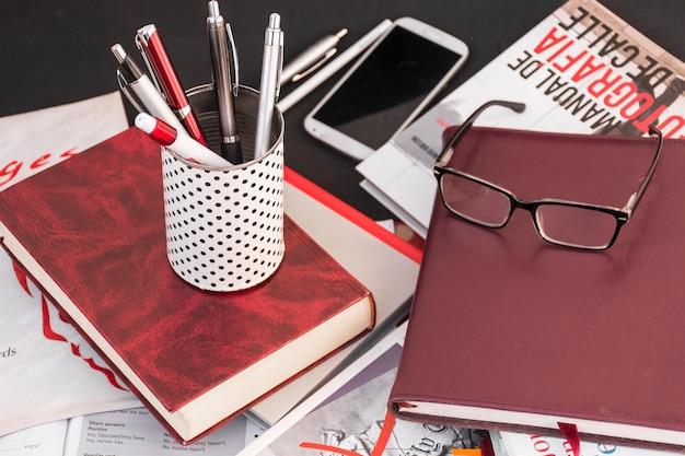 Canetas e óculos em livros