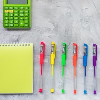 Canetas gel multicoloridas, caderno e calculadora