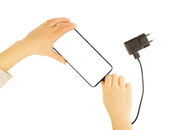 Canetas infantis inserem o plugue do carregador em um telefone celular, isolado em uma parede branca.