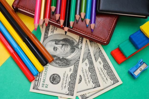 Canetas, lápis de cor, plasticina, livro, cem notas de dólar