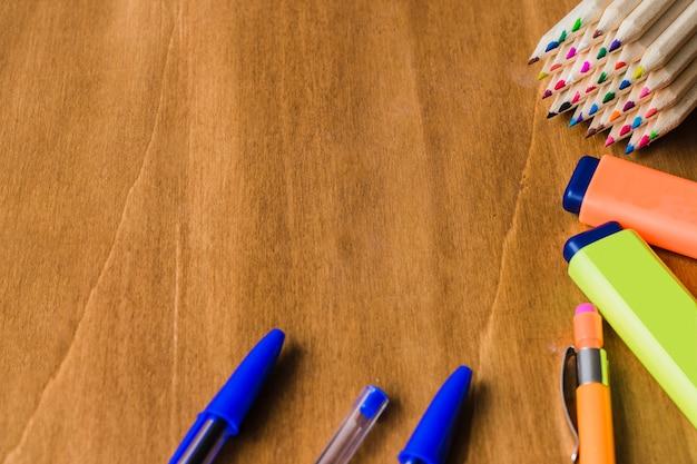 Canetas, lápis e marcadores na mesa de madeira