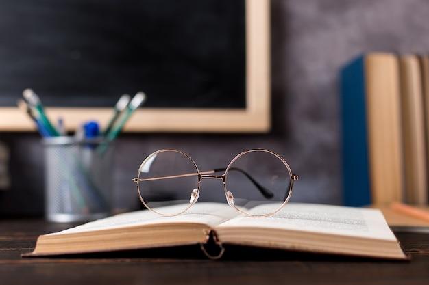 Canetas, lápis, livros e óculos sobre a mesa, contra o fundo do quadro-negro