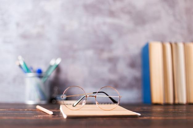 Canetas, maçã, lápis, livros e copos na mesa